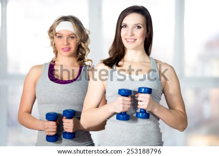 Active, healthy lifestyle, hobby, recreation, wellbeing, weight loss concepts. Two athletic girls doing exercises for waistline, side body bends with dumbbells in class - stock photo