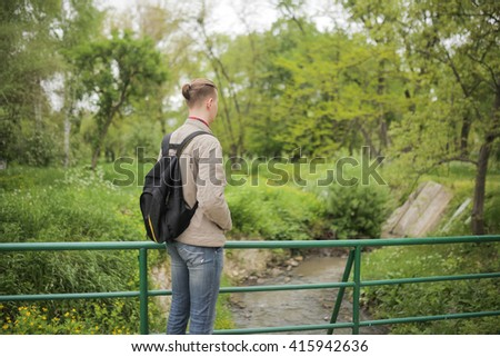 Active healthy man backpack in beautiful forest. Happy guy going on a hike looking in the sky. Man with hiking equipment walking in mountain forest. Park. Sports