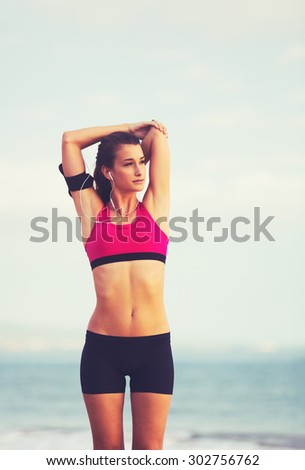 Active Healthy Sports Lifestyle with Modern Technology. Young attractive fitness woman with smart phone ready for workout. - stock photo