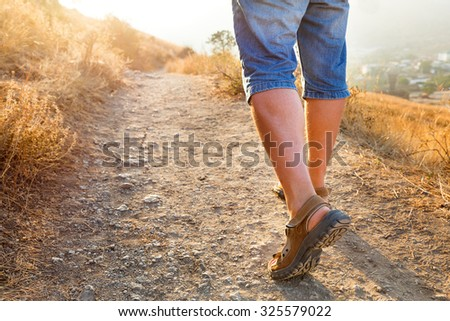 Active healthy travel - man in sports sandals climbs on the mountain. Closeup detail of male feet and stony path in sunset. Hiking in sunny day. Crimea, Russia. - stock photo
