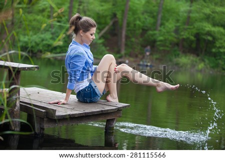Active healthy woman hiking in beautiful forest. Portrait of happy smiling young woman resting on lake.