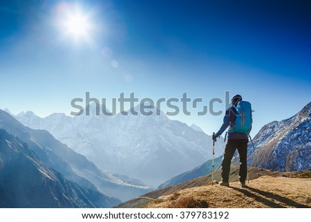 Active hiker hiking, enjoying the view, looking at mountain Himalaya landscape. mountaineering sport lifestyle concept  - stock photo