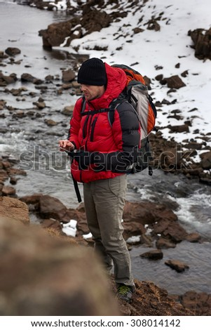 Active hiking man trekking by the river, using his mobile cell phone as a gps cold winter landscape snowy icy wilderness - stock photo