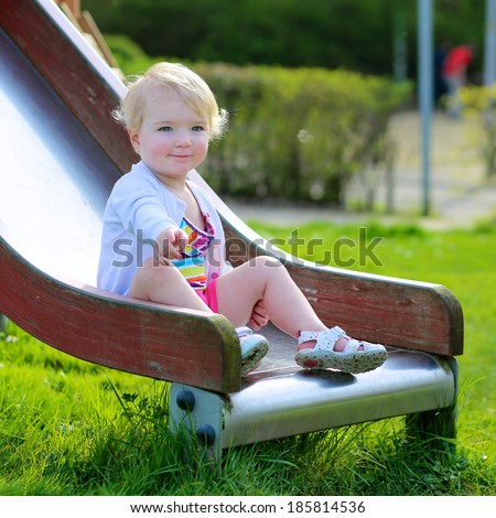 Active kid, adorable blonde toddler girl relaxing on the playground on a sunny summer day sitting on the slide - stock photo