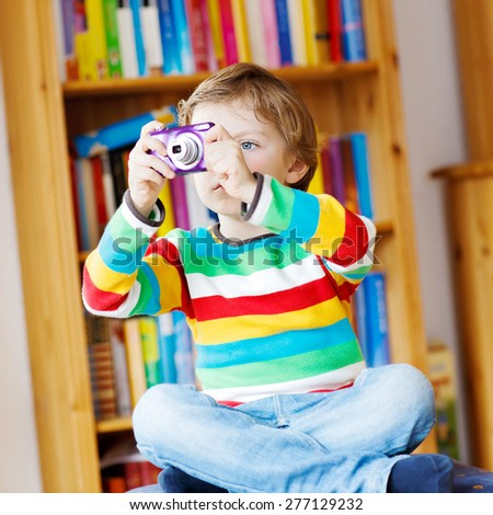 Active kid boy making photos with photocamera, indoors. Child wearing colorful shirt. Portrait in a daycare. - stock photo