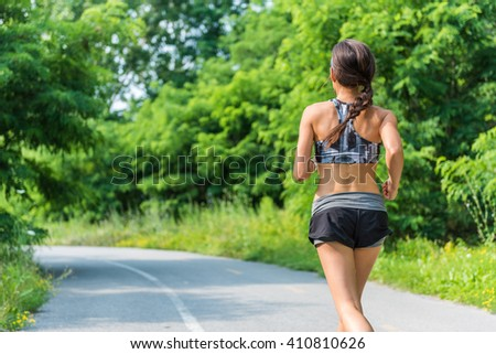 Active lifestyle girl runner running in summer city park living a healthy life. Jogger athlete woman from behind training cardio for weight loss of back thigh cellulite. Road to success to a fit body. - stock photo