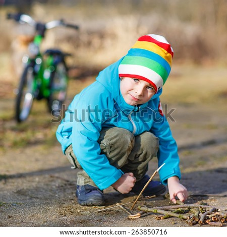 Active little boy playing with wooden sticks in city park. Happy child in colorful clothes, spring or autumn. Creative games with kids outdoors in nature. - stock photo