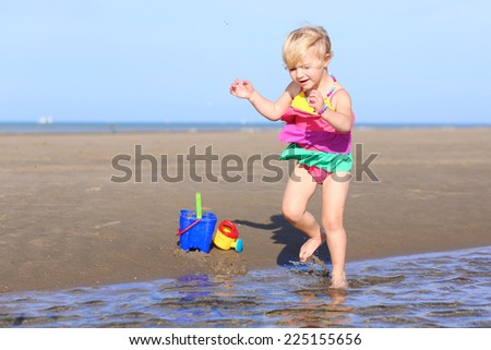 Active little child, adorable blonde toddler girl wearing colorful necklace and swimming suit playing on the beach at North Sea jumping and splashing in the water during low tide - stock photo