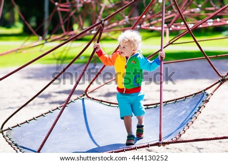 Active little child playing on climbing net and jumping on trampoline at school yard playground. Kids play and climb outdoors on sunny summer day. Cute boy on nest swing at preschool sport center. - stock photo