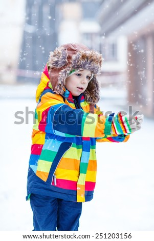 Active little preschool boy in colorful winter clothes having fun with snow, catching snowflakes, outdoors during snowfall on cold day. Active outoors leisure with children in winter. - stock photo