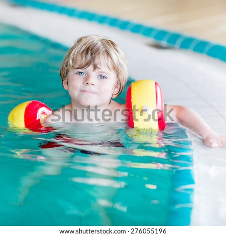 Active little toddler child, cute boy with water wings learning to swim in an indoor pool. Active and fit leisure for children. - stock photo