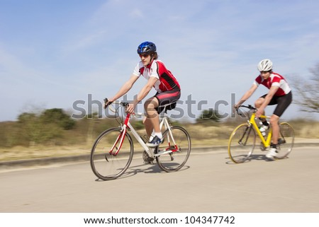 Active male athlete riding bicycles on an open country road - stock photo