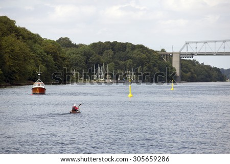 Active man kayaking on Little Belt close to old bridge and small harbor in Denmark - stock photo