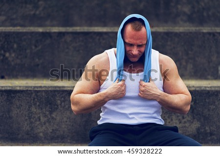 Active man resting after workout with towel. - stock photo