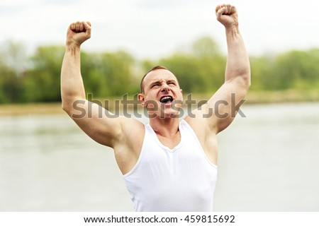 Active man with arms up wining. Shout. - stock photo