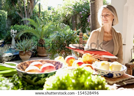Active mature attractive woman sitting in her home garden reading a cook book next to a table full of organic vegetables and fruit in abundance, during a sunny day outdoors. - stock photo