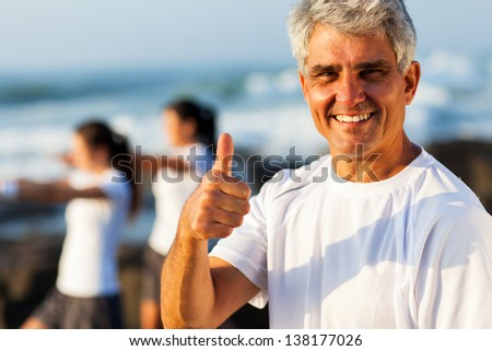 active mature man giving thumb up on beach with family exercising on background - stock photo