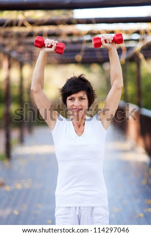 active middle aged woman working out with dumbbells - stock photo