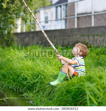 Active preschool kid boy fishing on a river with selfmade fishing rod  on sunny summer day. Happy child having fun. Active leisure for children outdoors. - stock photo