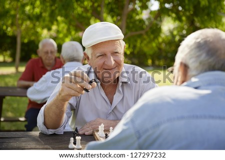 Active retired people, old friends and free time, two seniors having fun and playing chess game at park. Waist up - stock photo