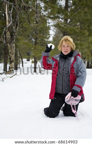 Active retired woman playing in the snow
