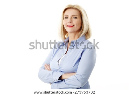 Active retired woman standing against white background while arms crossed and looking at camera.  - stock photo
