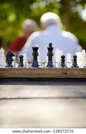 Active retirement, old friends and leisure, two senior men having fun and playing chess game at park. Focus on chessboard in foreground - stock photo