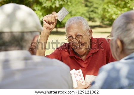 Active retirement, old people and seniors free time, group of three elderly men having fun and playing cards game at park - stock photo
