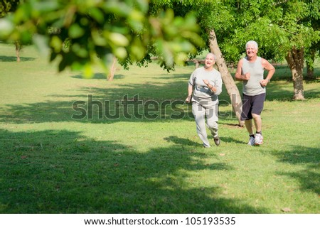 Active retirement, senior couple running and exercising in city park. Copy space