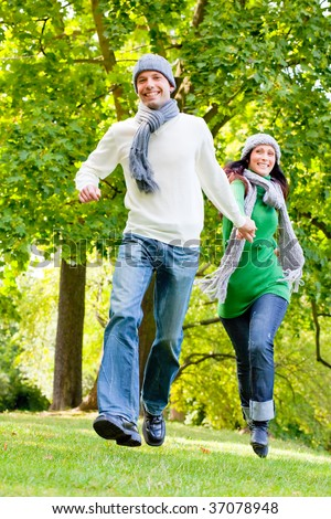 Active running couple through colorful parc with warm clothes and scarf - stock photo