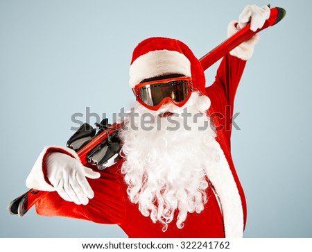 Active Santa Claus in goggle holding ski
