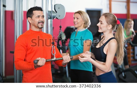Active satisfied smiling people  weightlifting training in modern health club