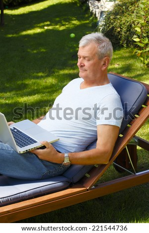 Active senior businessman working with laptop while sitting at home at garden.