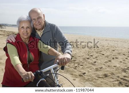 Active senior couple biking by the sea - stock photo