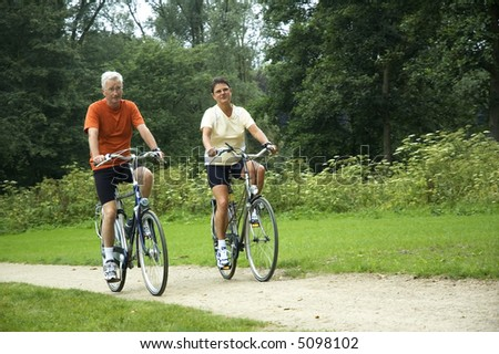 Active senior couple biking in the park. - stock photo