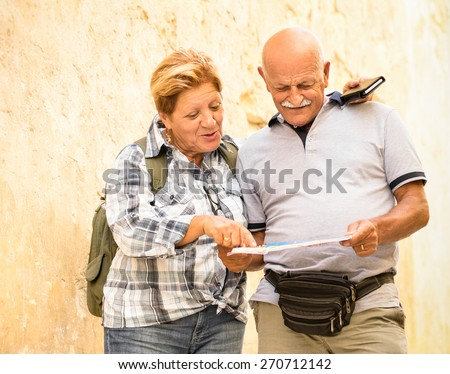 Active senior couple exploring old town of La Valletta with travel map - Concept of youthful elderly and tourist retired lifestyle without age limitation - Warm neutral color tones in cloudy shadow - stock photo