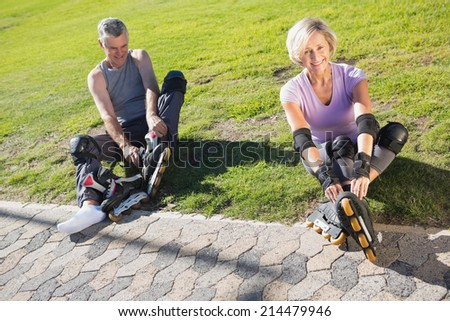 Active senior couple ready to go rollerblading on a sunny day - stock photo