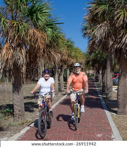 Active senior couple riding bikes on their Florida vacation. - stock photo