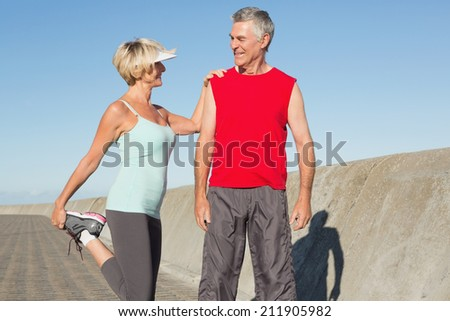 Active senior couple stretching before a jog on a sunny day - stock photo