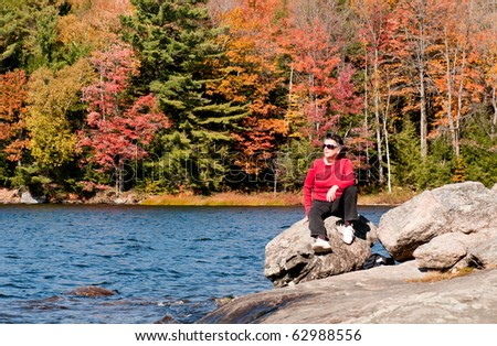 Active senior female hiker resting on a boulder