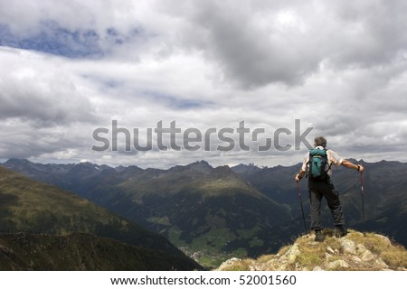 Active senior hiker standing at summit with hiking sticks and rucksack enjoying the stunning landscape of the Alps, Tyrol, Austria. - stock photo