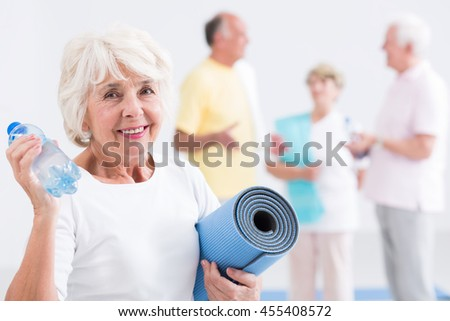 Active senior lady smiling, holding bottle of water and foam mattress
