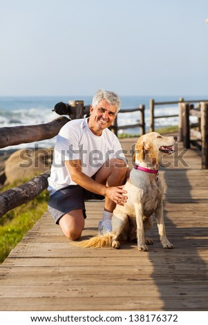 active senior man and his pet dog at the beach in the morning - stock photo