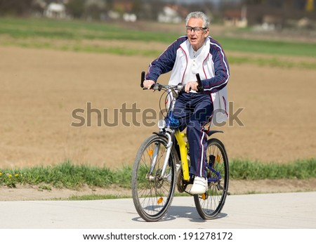 Active senior man riding a bicycle on countryside - stock photo