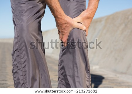 Active senior man touching his injured knee on a sunny day