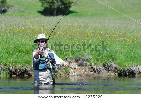 Active senior woman casting a fly-fishing rod in the Firehole River in Yellowstone Park.