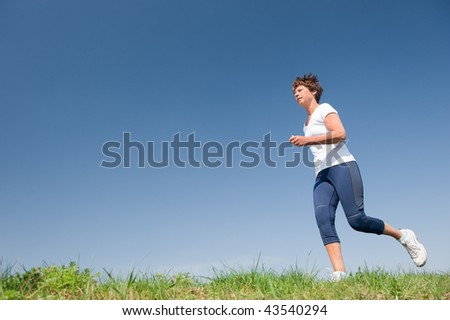 Active senior woman is running (jogging) in front of blue sky