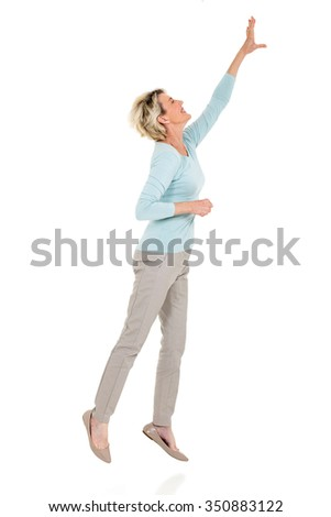 active senior woman jumping up and reaching out on white background - stock photo