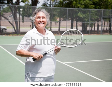 Active senior woman on the tennis courts. - stock photo