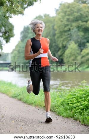 Active senior woman running - stock photo